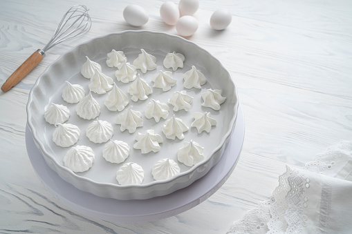 Meringue kisses in white homemade with egg white on white background