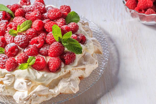 meringue pavlova  with whipped cream and fresh raspberries. - himbeer mascarpone dessert stock-fotos und bilder
