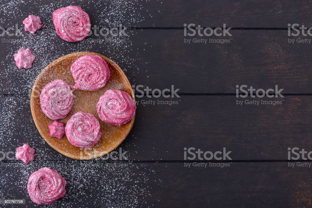 Meringues cookies on wooden plate and dark background stock photo