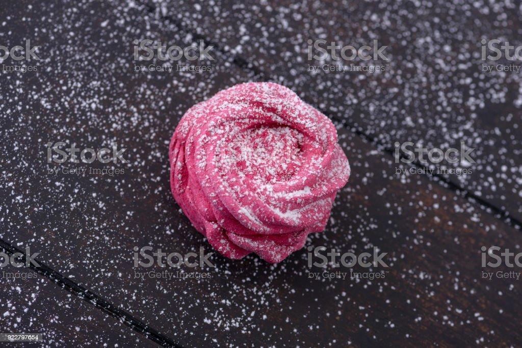 Meringues dark wooden background sprinkled with powdered sugar stock photo