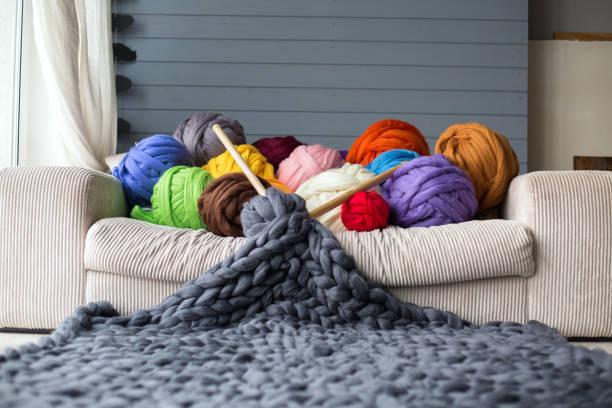bolas de lana de merino en la mentira multicolor en el blanco sofá con manta de lana gris de merino con agujas de madera - couch potato refrán en inglés fotografías e imágenes de stock