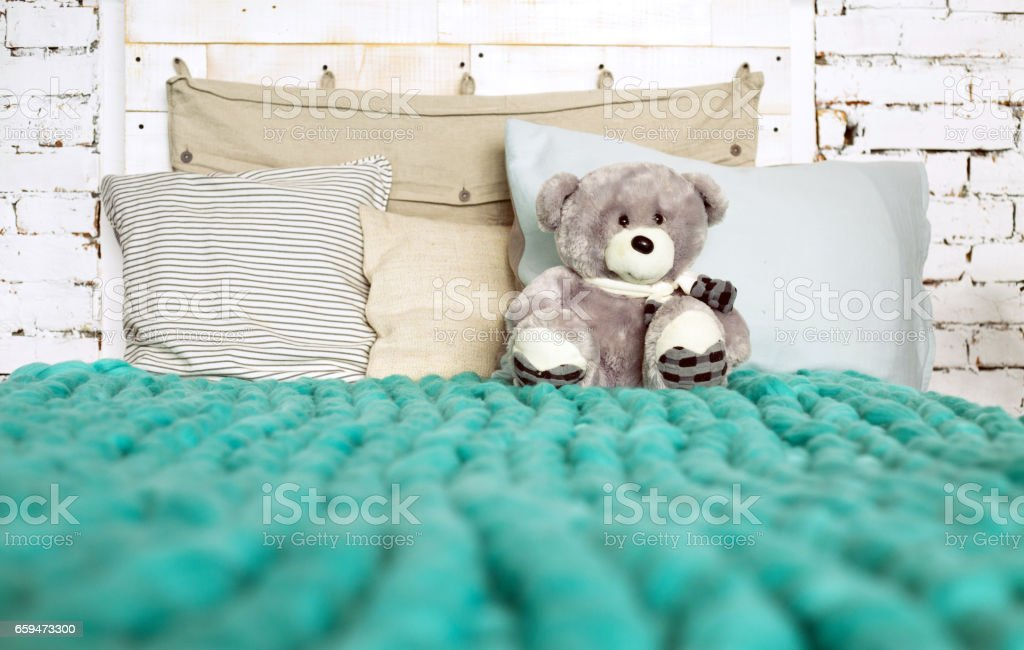 Merino wool blanket on bed with pillows in pastel colors and Teddy bear, loft interior stock photo
