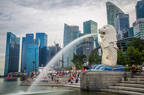 Merlion in Singapore Harbour Singapore, Singapore - October 1, 2016: Merlion statue fountain at Singapore Harbour with skyline in background merlion fictional character stock pictures, royalty-free photos & images