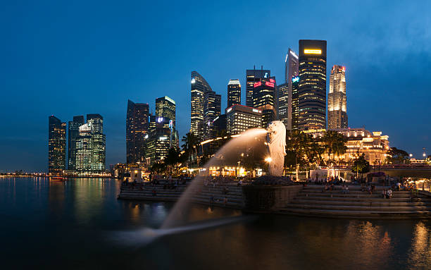 "Merlion Park in Panorama ""Singapore, Singapore - May 16, 2012: Tourists sitting at the steps of Merlion Park, enjoy the night scene of Marina Bay. A very popular view of Merlion during dusk hour with Centre Business District in background in panorama."" merlion statue stock pictures, royalty-free photos & images"