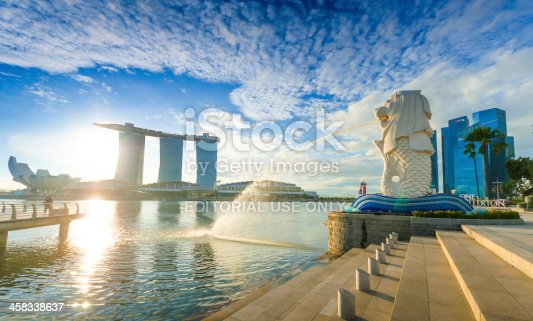 Singapore, Singapore - November 4, 2012: Tourist beside the Merlion statue fountain, iconic symbol of Singapore, overlooking the Marina Bay waterfront, the Esplanade Theatres, luxury hotels