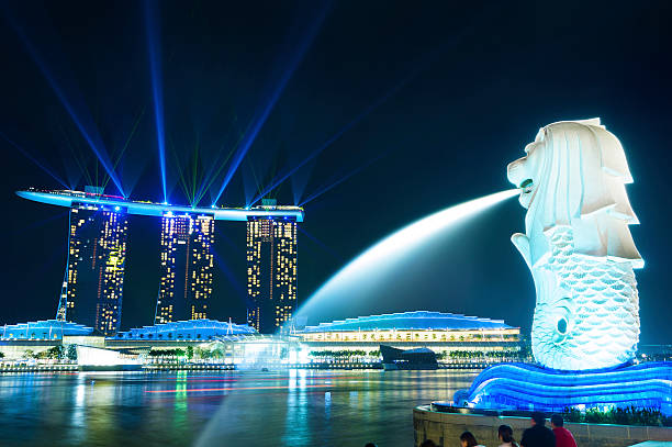 Merlion park Panorama Singapore, Singapore - November 5, 2012: Tourist beside the Merlion statue fountain, iconic symbol of Singapore, overlooking the Laser show of Marina Bay waterfront, the Esplanade Theatres, luxury hotels  merlion statue stock pictures, royalty-free photos & images