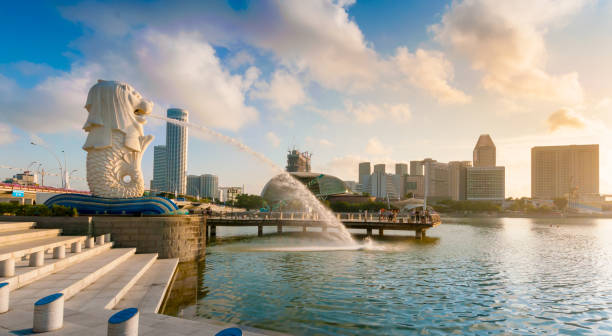 Merlion park Panorama Singapore, Singapore - 20 July, 2014: Tourist beside the Merlion statue fountain, iconic symbol of Singapore, overlooking the Marina Bay waterfront, the Esplanade Theatres, luxury hotels merlion statue stock pictures, royalty-free photos & images