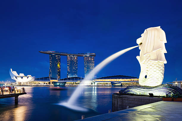 "Merlion Statue, Singapore ""Singapore, Singapore - June 9, 2011: Merilon Statue at Marina Bay at twilight with Marina Bay Sands Hotel and Art Science Museum in the background. Tourists shooting the statue on the left side."" merlion statue stock pictures, royalty-free photos & images"