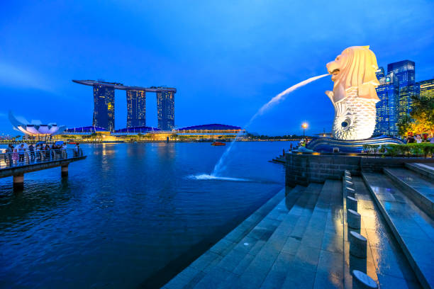 Merlion Statue Singapore Singapore - April 27, 2018: reflecting statue Singapore Merlion in Marina Bay sea. Merlion has a lion's head and fish body and it's spouting water from its mouth. Marina Bay Sands towers in skyline. merlion statue stock pictures, royalty-free photos & images