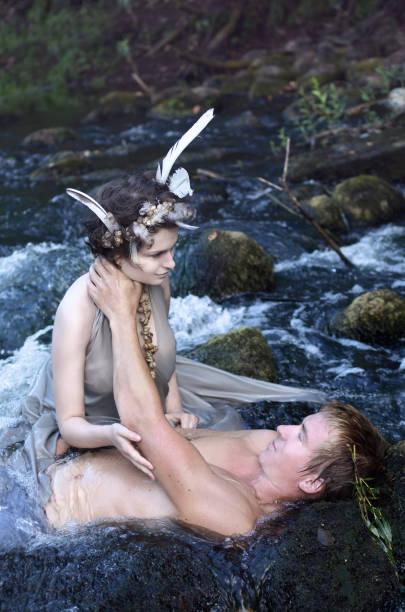 meerjungfrau und der mann auf den felsen im wasserfall - meerjungfrau wellen stock-fotos und bilder