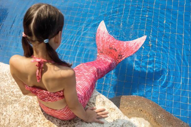mermaid girl with pink tail on rock at poolside put feet in water - tail stock photos and pictures