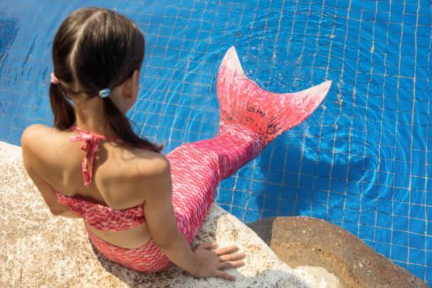 Niña de sirena con cola rosa en roca junto a la piscina pone pies en el agua - foto de stock