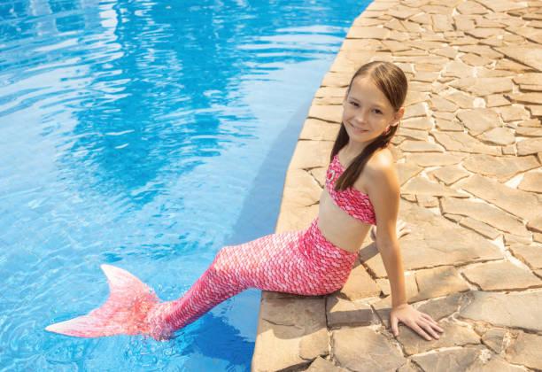 meerjungfrau-mädchen mit rosa schweif auf felsen am pool legen die füße im wasser. ansicht von oben - meerjungfrau kleid stock-fotos und bilder