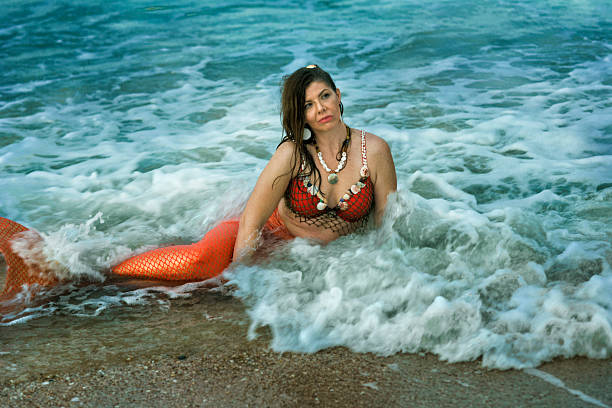 mermaid rests in shallow waves in atlantic ocean - meerjungfrau wellen stock-fotos und bilder