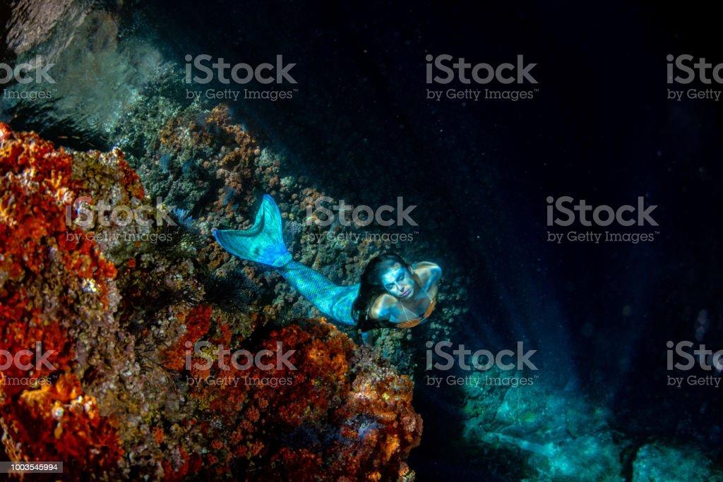 black hair Mermaid swimming underwater in the deep blue sea and...