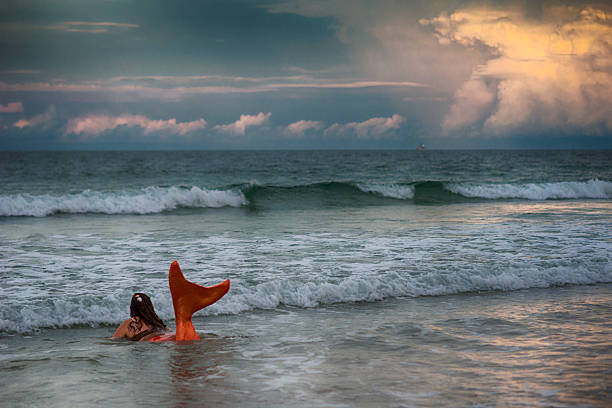 mermaid with orange tail in ocean at sunset - meerjungfrau wellen stock-fotos und bilder