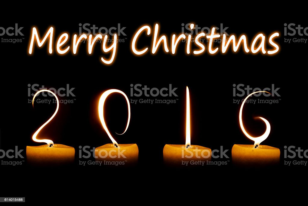 Merry Christmas 2016 written with candle flames on black background stock photo