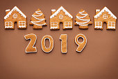 Merry Christmas and Happy New Year 2019. Gingerbread cookies on brown background, top view