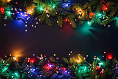 Christmas and New Year background with copy space for text. Fairy lights and decor of fir branches and confetti. Flat lay, top view