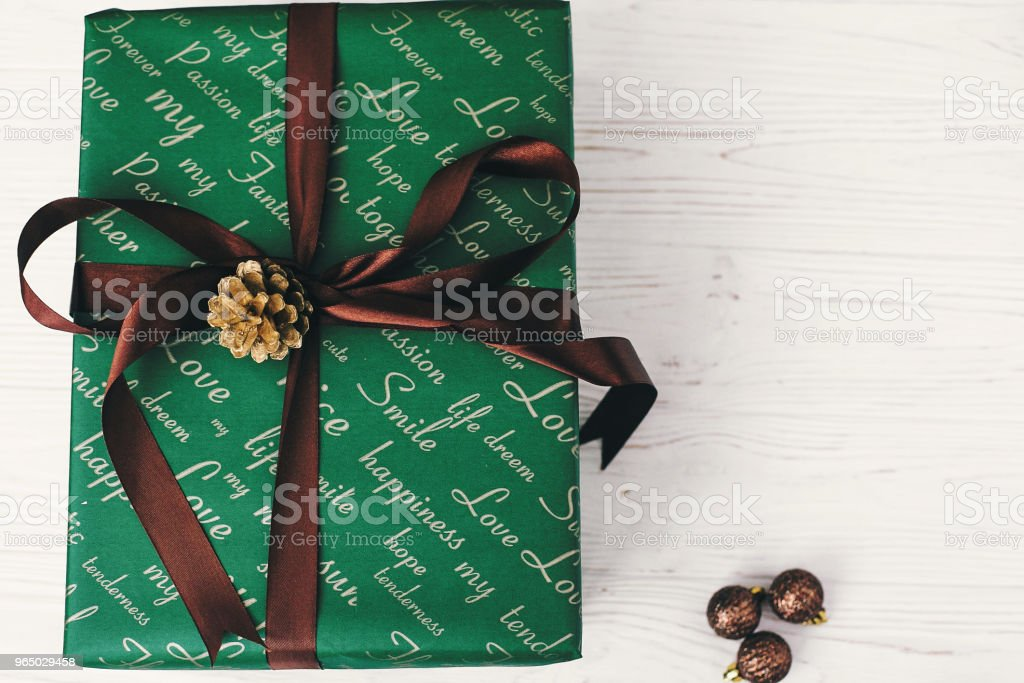 merry christmas and happy new year concept. stylish wrapped gift box with ornaments and golden pine cone. seasonal greetings, happy holidays. xmas present flat lay royalty-free stock photo