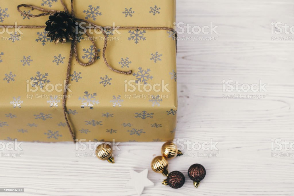merry christmas and happy new year concept. stylish wrapped gift box with ornaments and golden pine cone. space for text. seasonal greetings, happy holidays. xmas present royalty-free stock photo