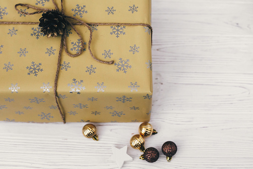 Merry Christmas And Happy New Year Concept Stylish Wrapped Gift Box With Ornaments And Golden Pine Cone Space For Text Seasonal Greetings Happy Holidays Xmas Present Stock Photo - Download Image Now