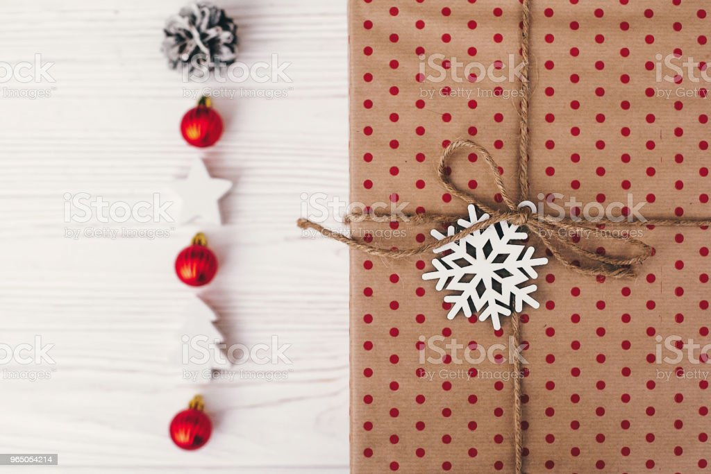 merry christmas and happy new year concept. stylish wrapped gift box top view, with ornaments and tree snowflake. simple craft paper. seasonal greetings, happy holidays royalty-free stock photo