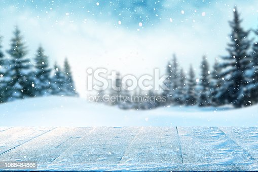 istock Merry christmas and happy new year greeting background with table .Winter landscape with snow and christmas trees 1068484866