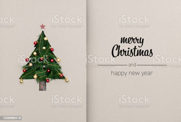 Photo of Merry Christmas and happy new year greetings in vertical top view cardboard with natural eco decorated christmas tree pine.Ecology concept.Xmas winter holiday season social media card background