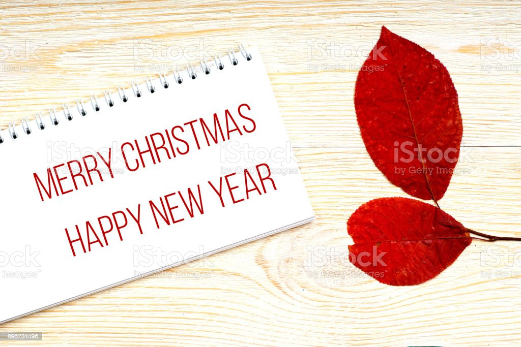 Merry Christmas and Happy New Year greetings with red aspen leaves stock photo