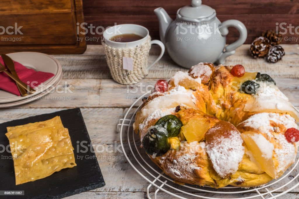 Merry Christmas cake with nuts and coscoroes. Bolo Rei is a traditional Xmas cake with fruits raisins nut and icing on wooden table. stock photo