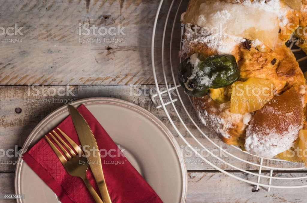 Merry Christmas cake with nuts - Bolo Rei is a traditional Xmas cake with fruits raisins nut and icing on wooden table. stock photo