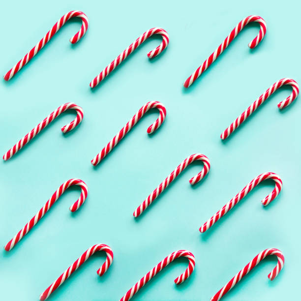 Merry Christmas candy can in row on blue background. Flat lay. Square image. Merry Christmas candy can in row on blue background. Flat lay. Square image. Pattern. candy cane stock pictures, royalty-free photos & images