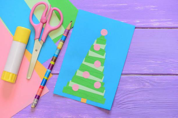 merry christmas card, schere, klebestift, bleistift, farbpapier auf lila holztisch. lustige grußkarte mit einem weihnachtsbaum. einfache weihnachtskarten kinder können aus papier zu machen. ansicht von oben - winterdeko basteln stock-fotos und bilder