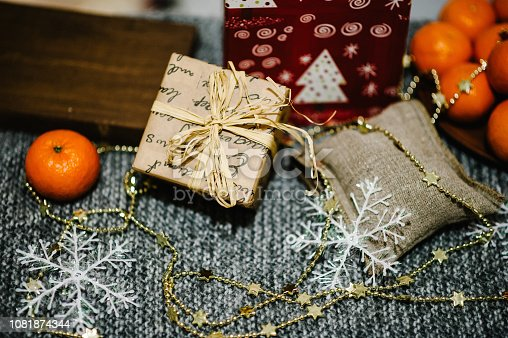 istock Merry Christmas, Celebration Concept. Tangerines, gift box, snowflakes, rustic stylish sack on gray knitted background. space for text, design. Happy Holidays. top view. 1081874344