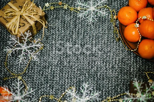 istock Merry Christmas, Celebration Concept. Tangerines, gift box, snowflakes, rustic stylish on gray knitted background. space for text, design. Happy Holidays. top view. winter flat lay image. 1081874352