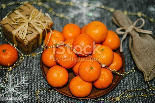 istock Merry Christmas, Celebration Concept. Tangerines, gift box, snowflakes, rustic stylish sack on gray knitted background. space for text, design. Happy Holidays. top view. 1081874358