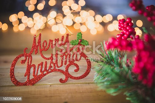 Text reading Merry Christmas on a wood background with Christmas lights