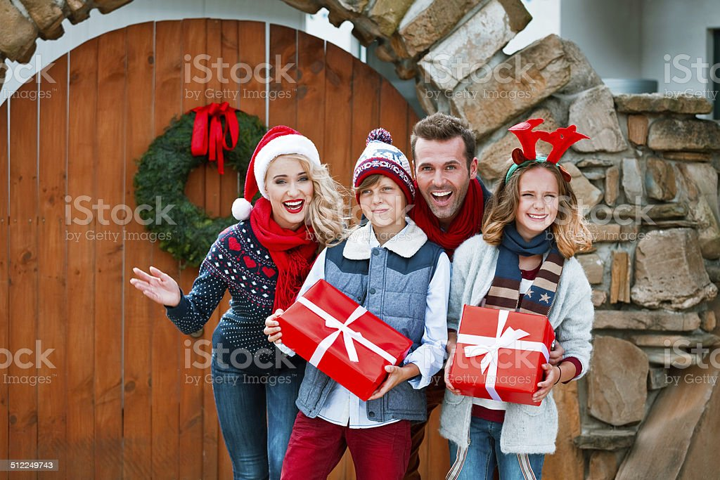 Merry Christmas, Family Portrait Winter portrait of happy family standing in front of entrance door and smiling at camera. Children holding christmas gifts. 10-11 Years Stock Photo
