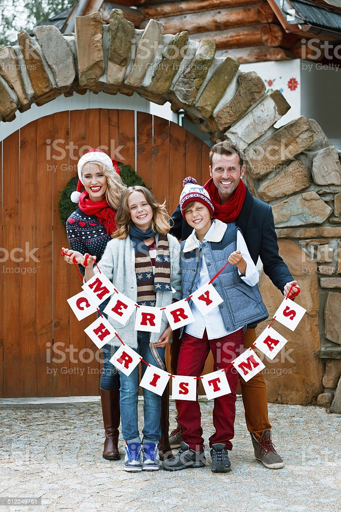Merry Christmas, Family Portrait Winter portrait of happy family: parents and children standing in front of entrance door, holding Merry Christmas wishes and smiling at camera. 10-11 Years Stock Photo
