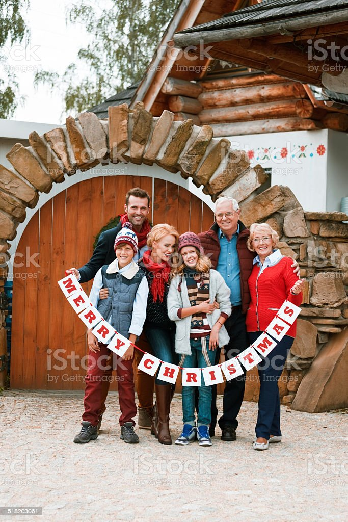 Merry Christmas, Family Portrait Winter portrait of happy multi generation family: grandparents, parents and children standing in front of entrance door and holding Merry Christmas wishes and smiling at camera. Active Seniors Stock Photo