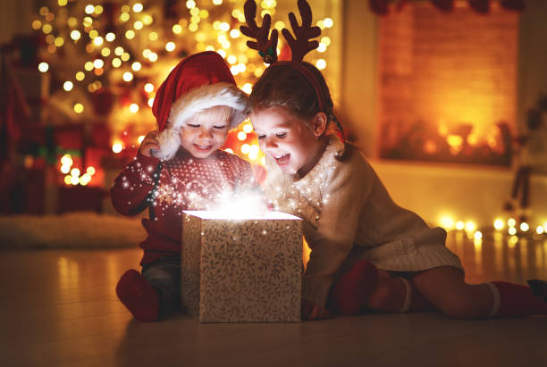 merry christmas! happy children with magic  gift  at home - christmas background стоковые фото и изображения