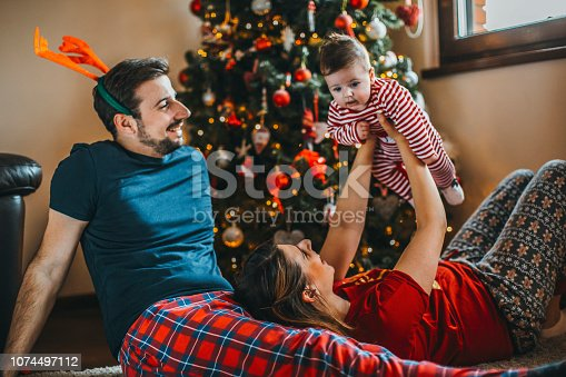 868220646istockphoto Merry Christmas! happy family mother father and child with gifts near tree 1074497112