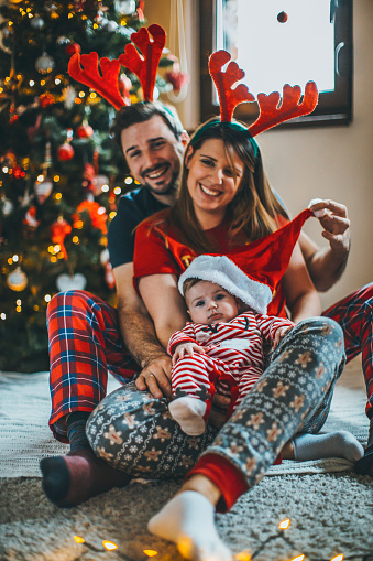 868220646 istock photo Merry Christmas! happy family mother father and child with gifts near tree 1074499500