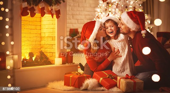 istock Merry Christmas! happy family mother father and child with gifts near tree 873882102