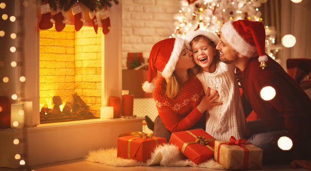 merry christmas! happy family mother father and child with gifts near tree - christmas families stock photos and pictures