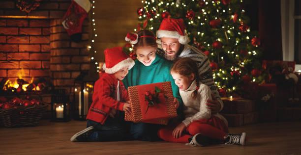 vrolijk kerstfeest! gelukkige familie moeder vader en kinderen met magische geschenk in de buurt van boom thuis - christmas family stockfoto's en -beelden