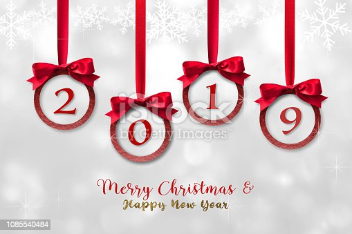 istock 2019 Merry Christmas, Happy New Year celebration with red ribbon and glittering bauble ball xmas holiday ornament decoration hanging on sparkling silver white snow flake white winter background 1085540484