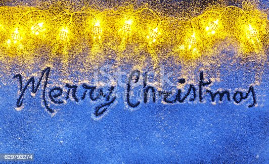 613303142 istock photo Merry Christmas letters handdrawn on snow surface with Garlands 629793274