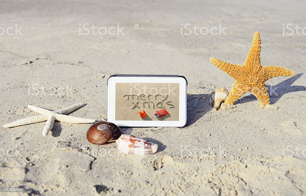 Merry Christmas Message on Tablet at the Beach royalty-free stock photo